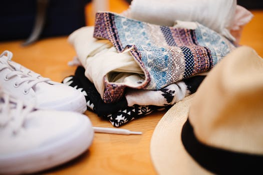 Brown Fedora Hat Beside White Sneakers and Blue Textile