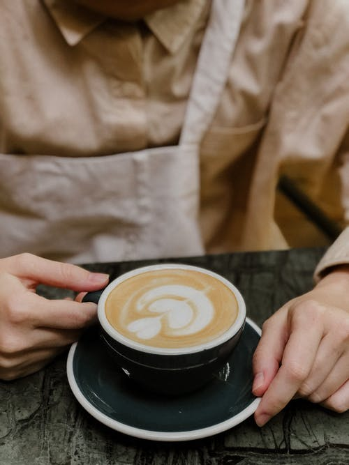 Crop barista with cup of coffee