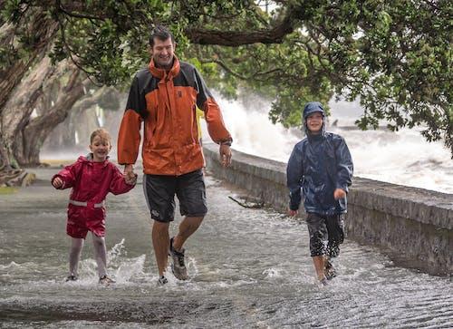 Foto profissional grátis de brincar, chuva, família, mar