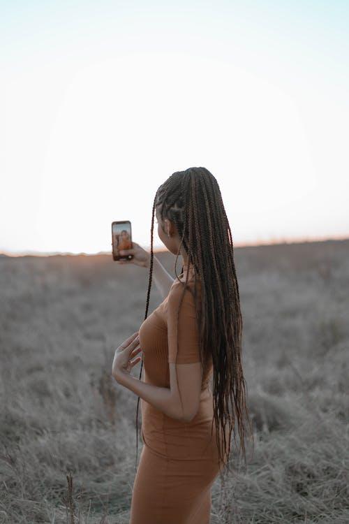 Woman in White Bikini Top Holding Smartphone