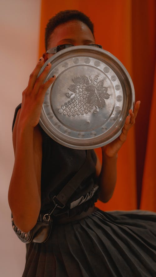 Person Holding Round Silver Container