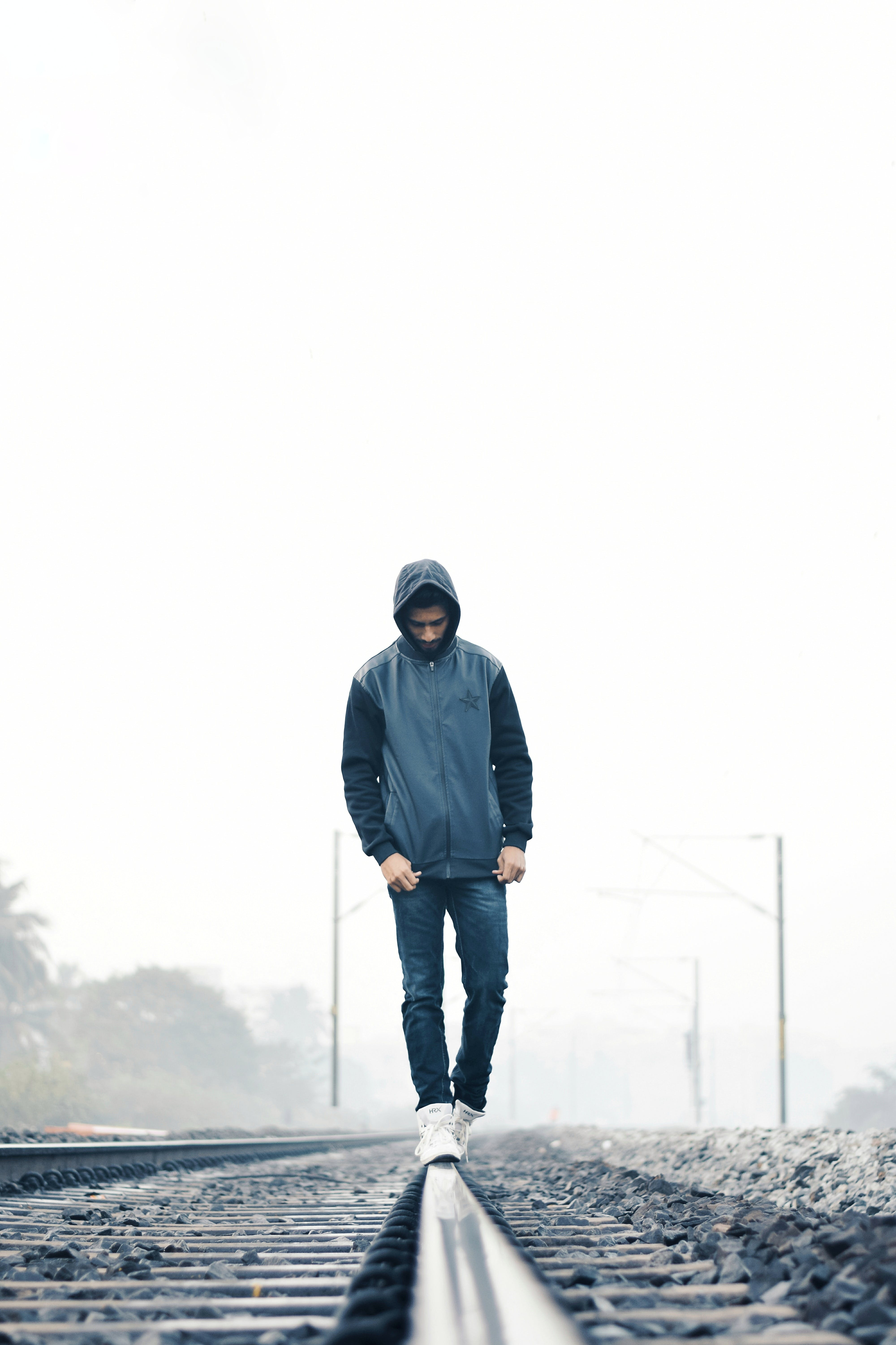 Man Wearing Gray and Black Zip-up Hoodie With Black Denim Jeans and White Shoes Walking on Train Railing Behind White Fog