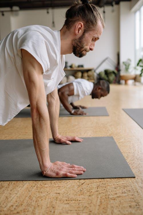 Man in White Shirt Doing Push Ups on the Yoga Mat