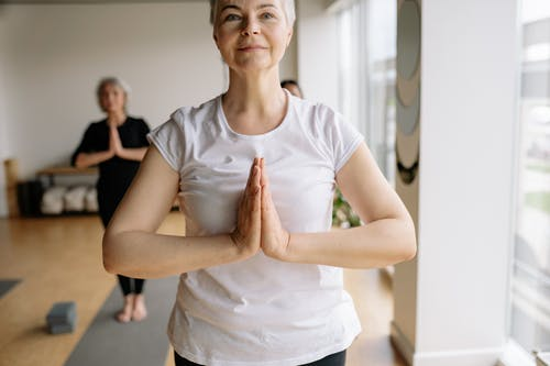 Shallow Focus Photo of a Woman in White Shirt Doing Yoga