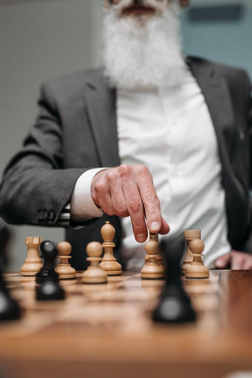 Man in Black Suit Jacket Holding Brown Wooden Chess Piece