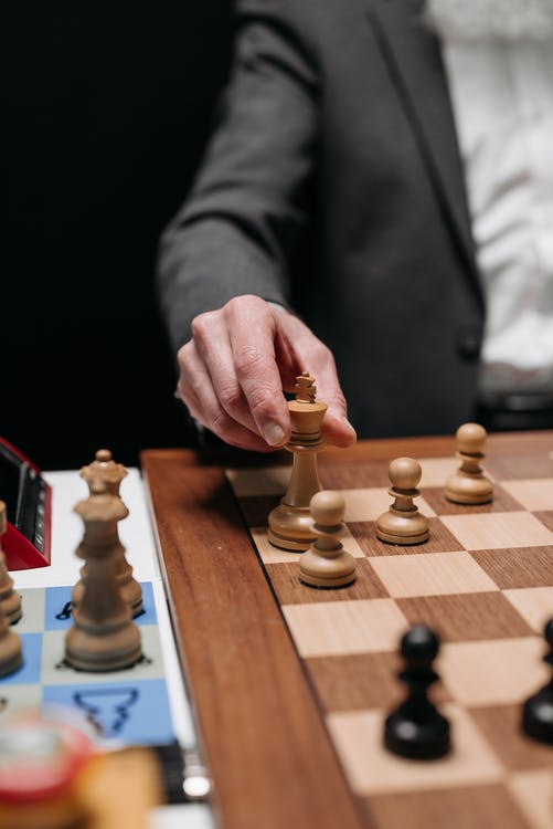 Person Wearing a Coat Playing Chess