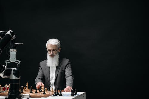 Man in Black Suit Jacket Playing Chess