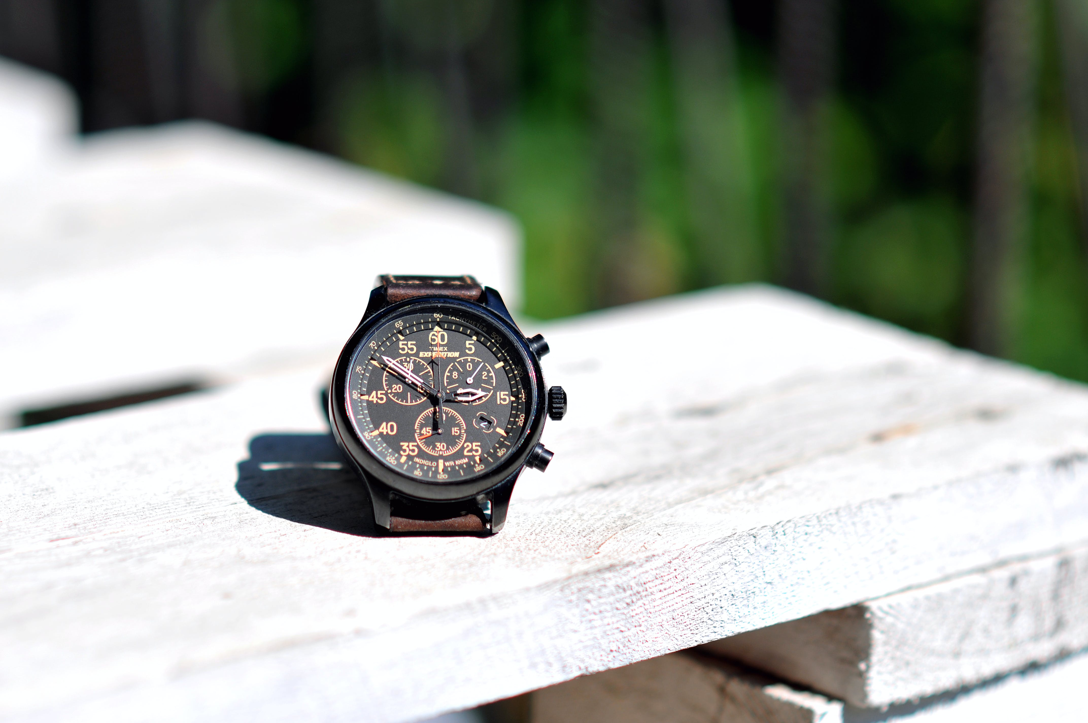 Round Black Chronograph Watch on White Wooden Board