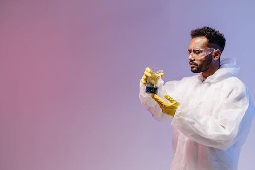 Man in White Dress Shirt Holding Yellow Bottle