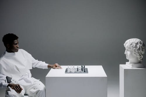A Man Playing Chess Against a Head Statue