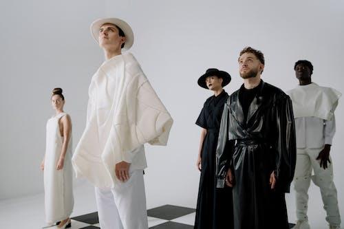 Man in White Thobe Standing Beside Woman in Black Dress