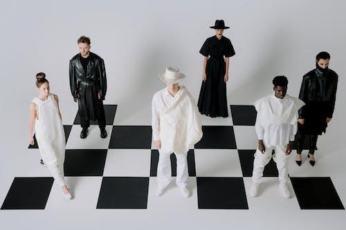 Man in Black Blazer Standing Beside Woman in White Dress