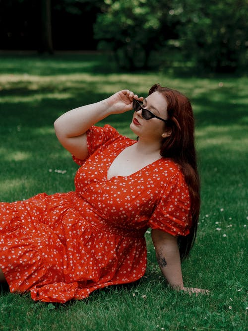 Woman in Red and White Floral Dress Wearing Black Sunglasses