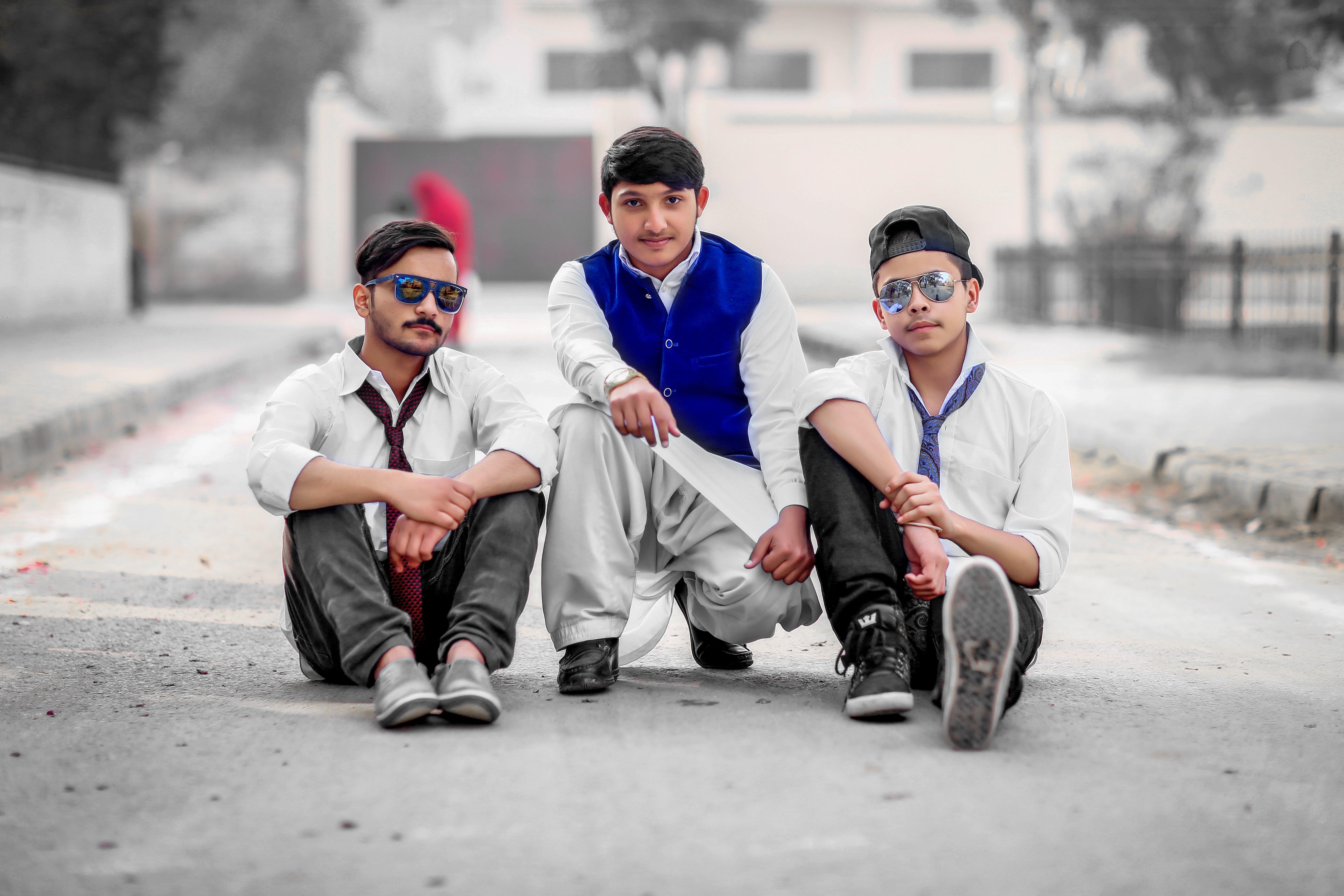 Three Men Sitting on Gray Concrete Road
