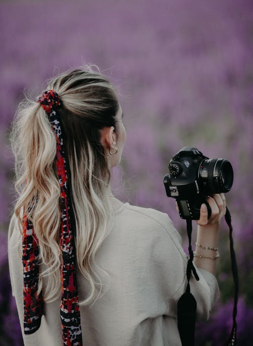 Back View of a Woman Holding a Black Dslr Camera