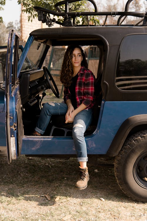 Woman in Red and Black Plaid Shirt and Blue Denim Jeans Sitting on Blue Car