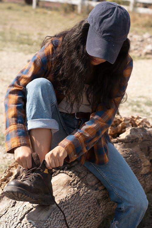 Woman in Blue Denim Jacket and Black Cap Sitting on Brown Rock