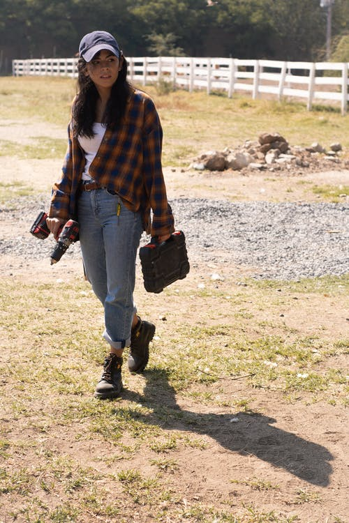 Woman in Red and Black Plaid Long Sleeve Shirt and Blue Denim Jeans Carrying Brown Leather