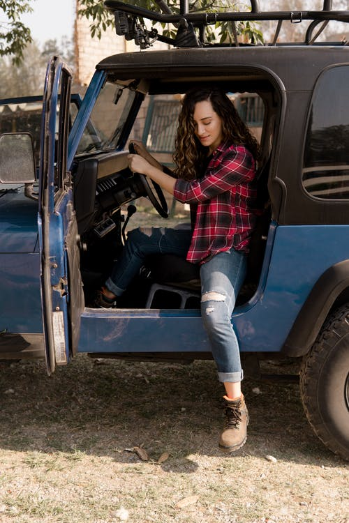 Woman in Red and White Plaid Shirt and Blue Denim Jeans Leaning on Blue Car