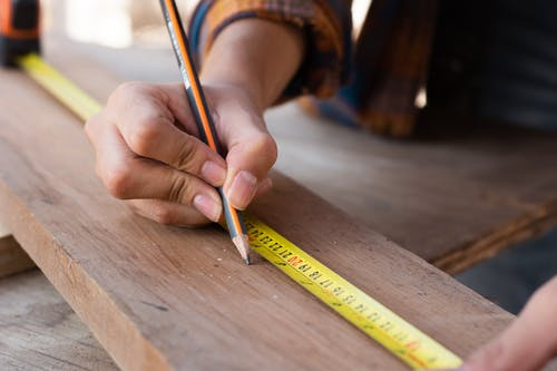 Woman Measuring with Yellow Pencil on Board