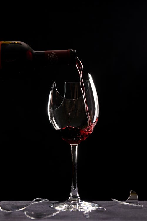 Close-Up Photo of a Red Wine Poured in a Broken Wine Glass
