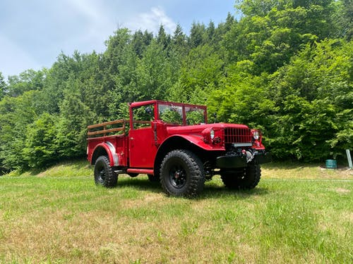 A Red Jeep on Green Grass Field