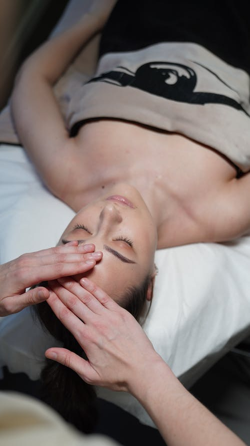 Woman in Black Tank Top Lying on Bed