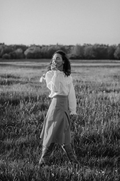 Wanita Berbaju Putih Lengan Panjang Berdiri Di Lapangan Rumput