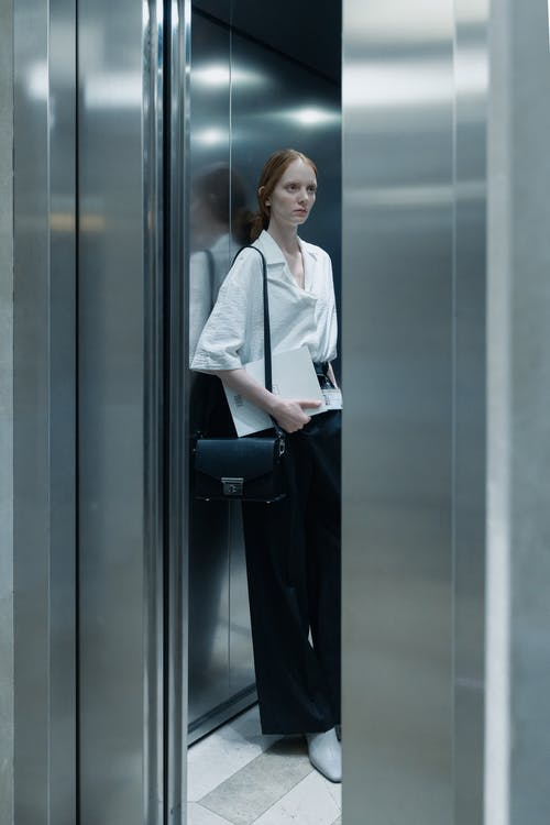 A Woman in White Button-Up Shirt Standing inside the Elevator
