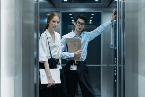 Employees in Corporate Attire Looking at Camera while Standing inside the Elevator
