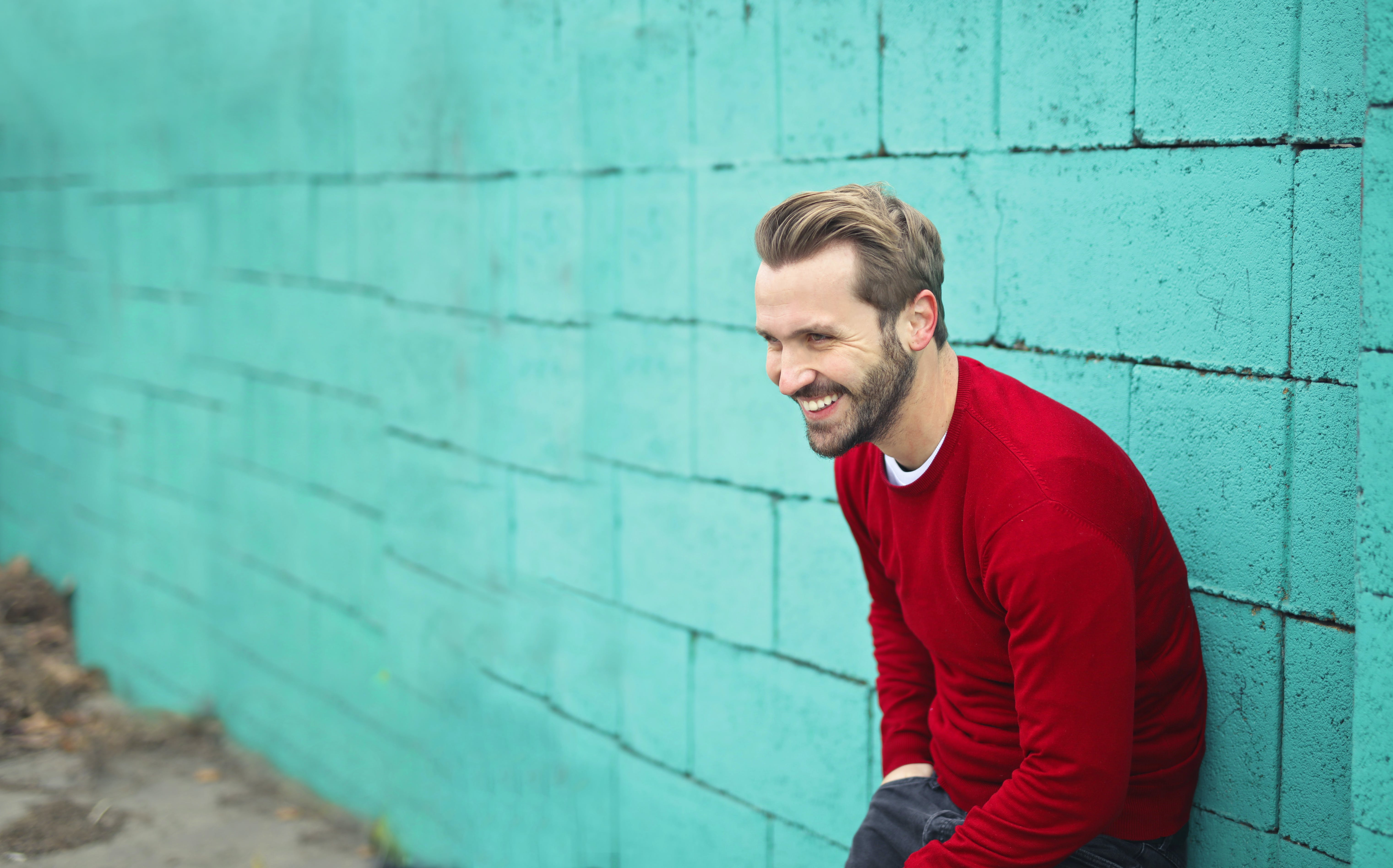 Man Wearing a Red Sweater Leaning on a Blue Wall