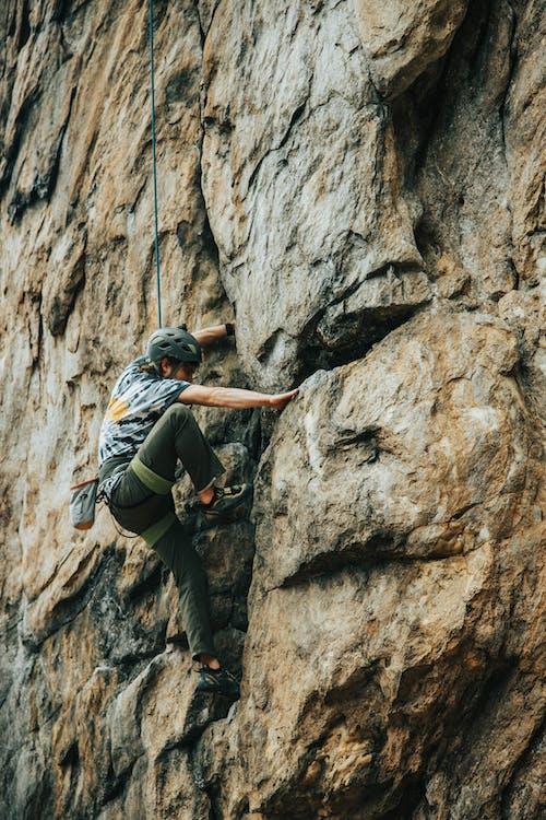 Man in Black Jacket Climbing on Gray Rock
