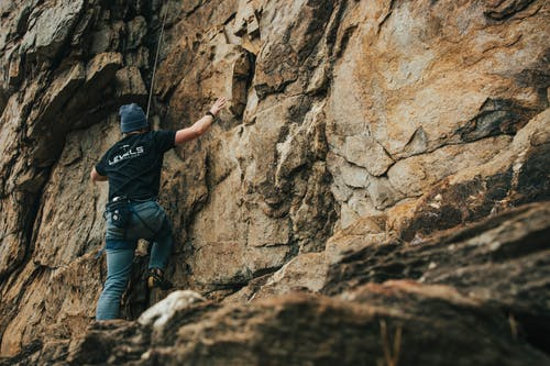 Man in Black Shirt Climbing Rocks