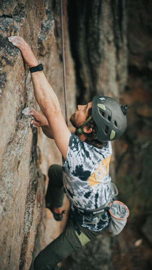 Person in Black and White Skull Print Shirt Climbing on Brown Tree