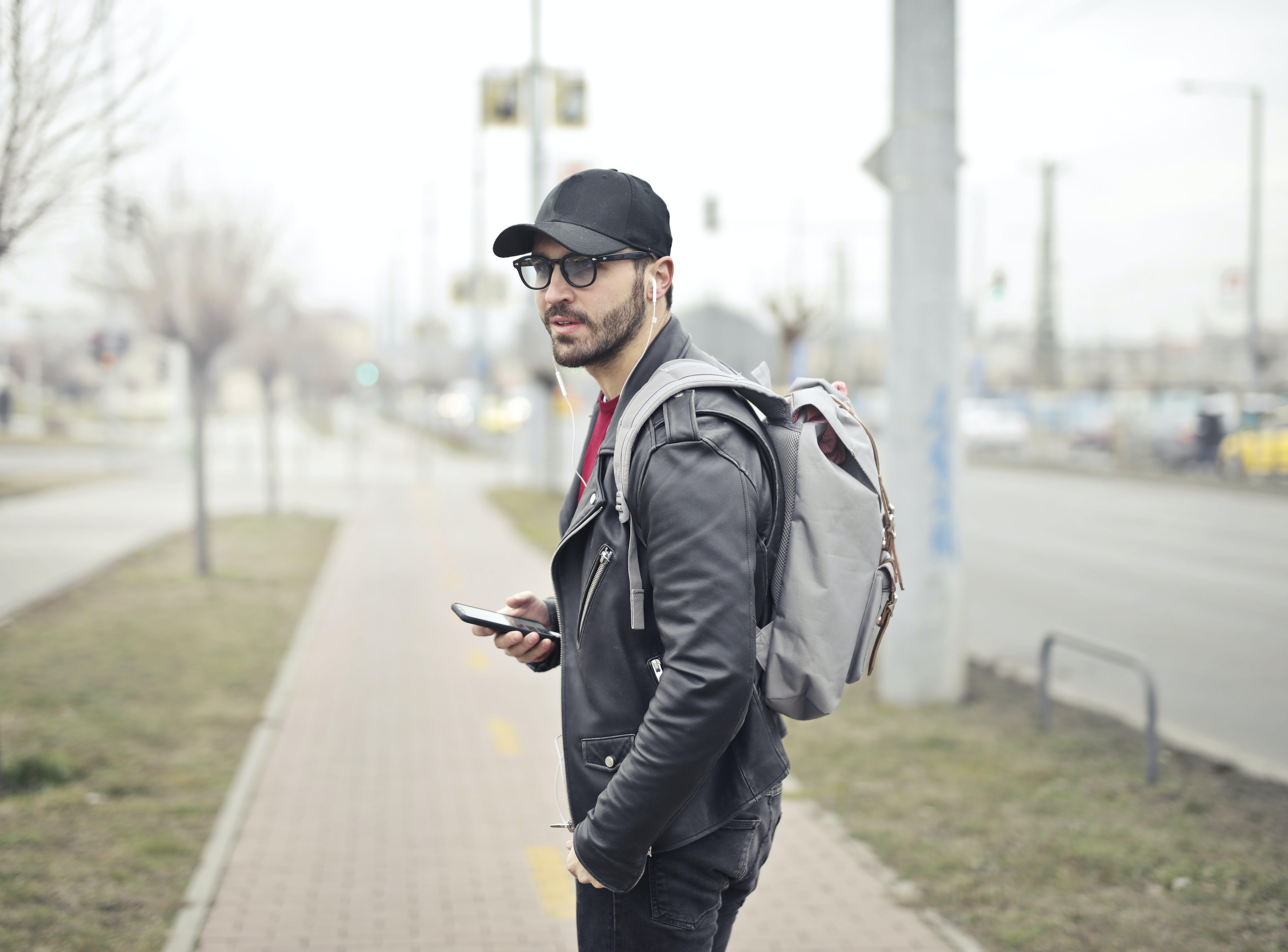 Man Wearing Black Leather Jacket Holding Smartphone