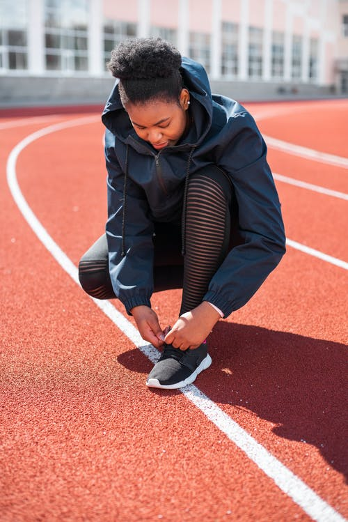 Woman Tying Shoes on a Track