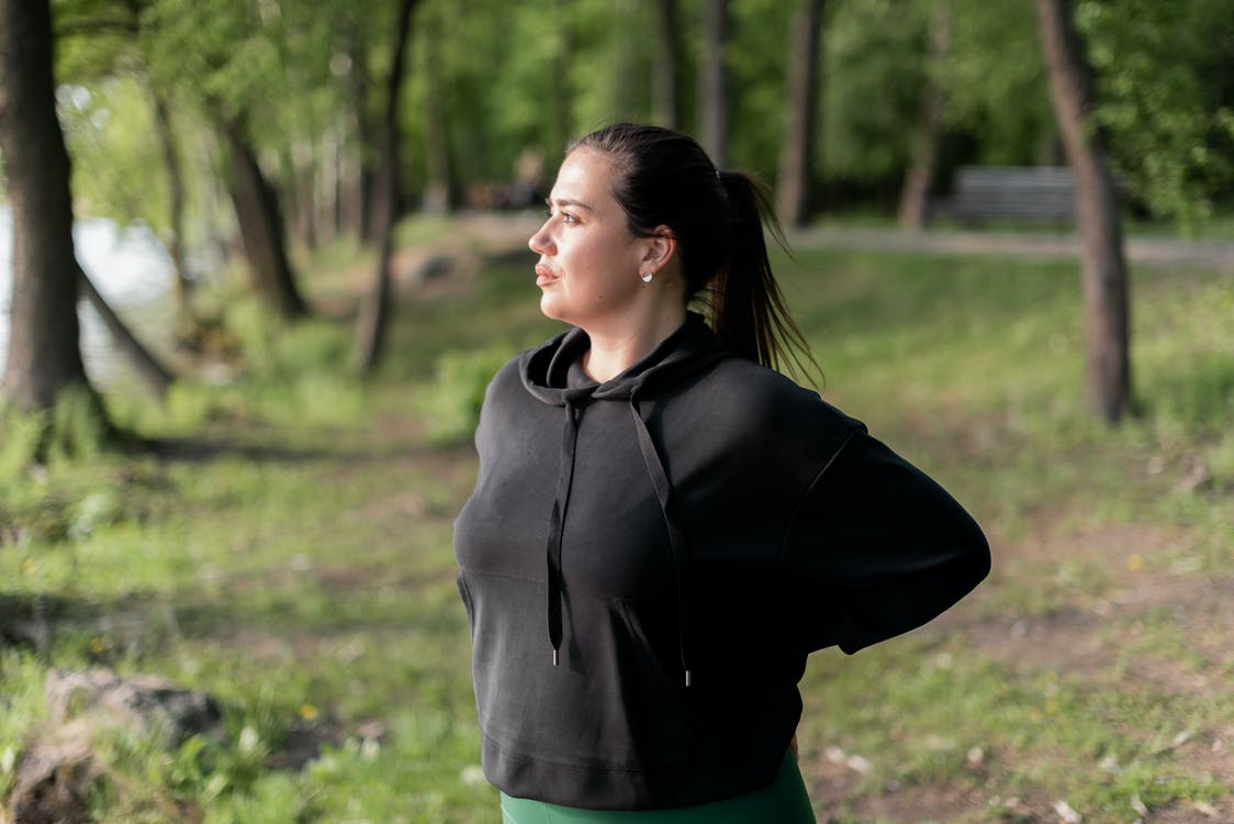 Woman in Black Hoodie Standing on Green Grass Field