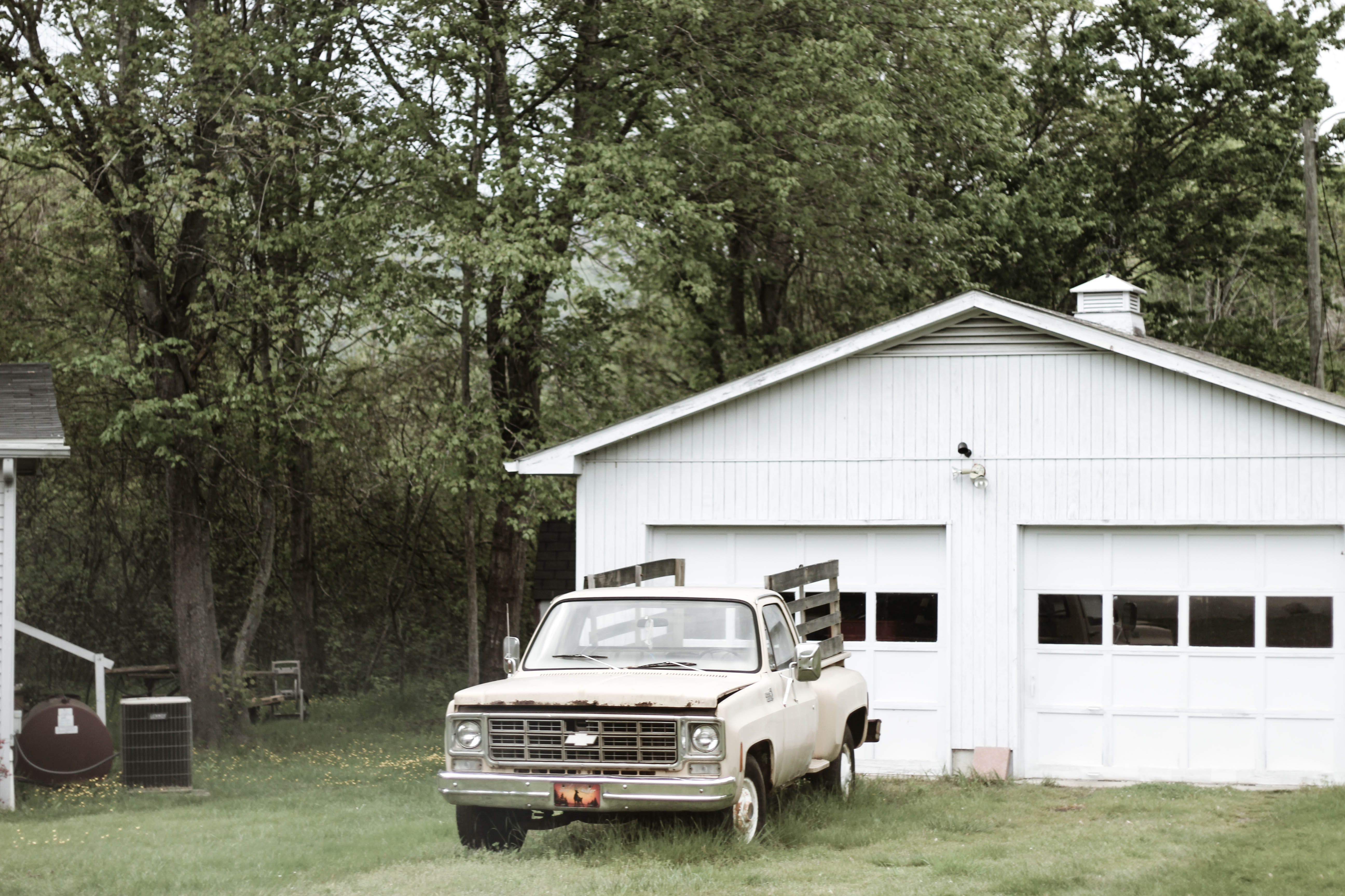 Gray Chevrolet Car Parked Near White Shed
