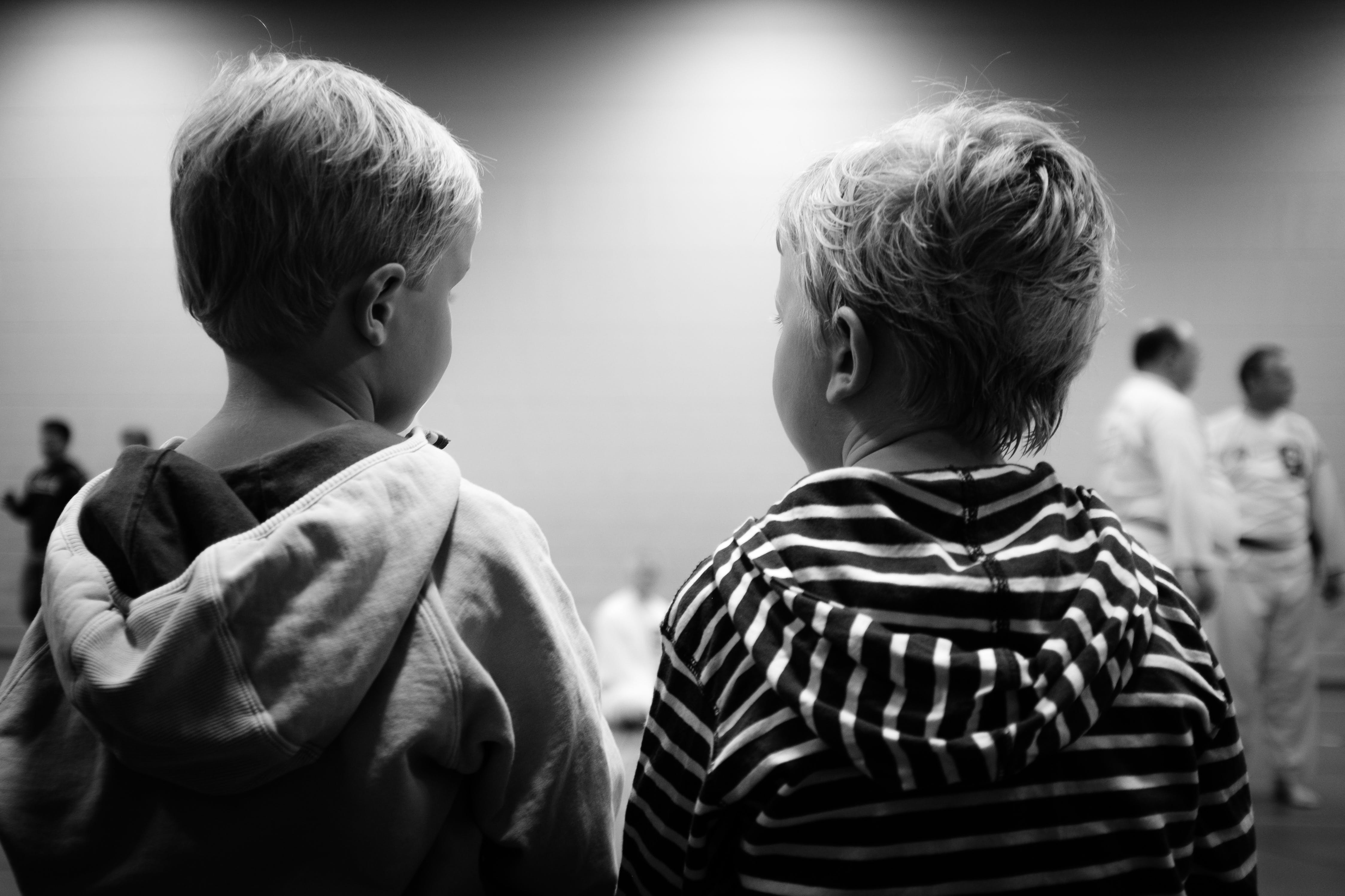 Grayscale of Two Boys Sitting Beside Each Other