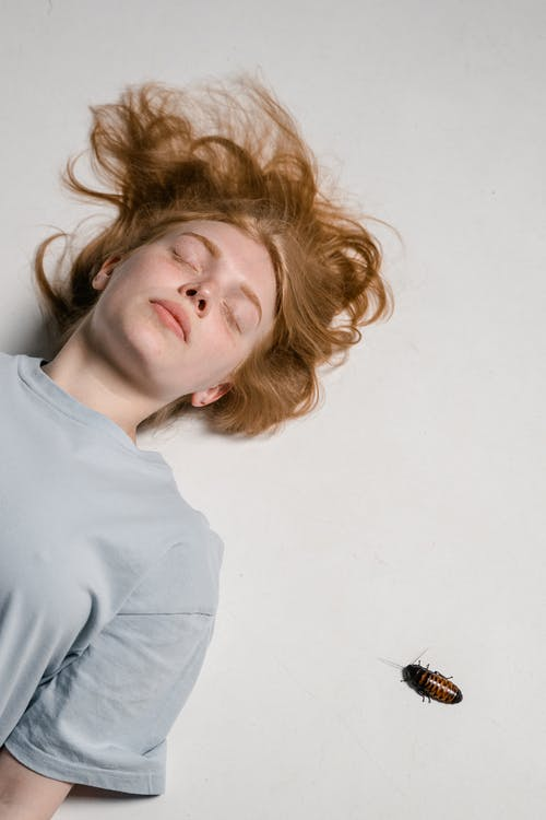 Close-Up Photo of a Fearful Woman Lying Down while Overcoming Her Fear of Cockroaches