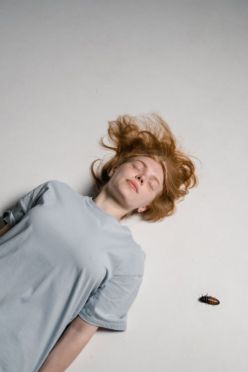 A Fearful Woman Lying Down while Overcoming Her Fear of Cockroaches