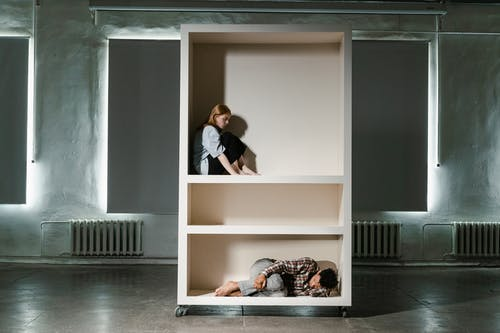 A Man and Woman Looking Lonely in a Cabinet