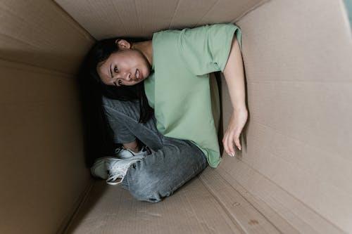 A Fearful Woman Having Claustrophobia in a Cardboard Box