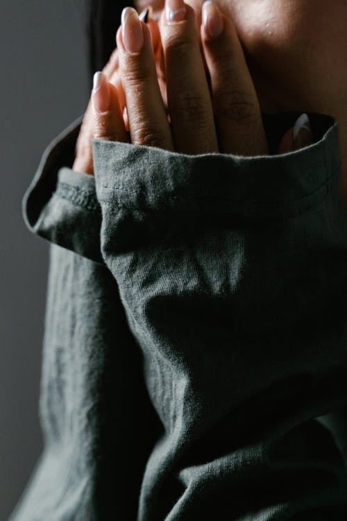 Close-Up Photo of a Fearful Person Covering Her Face