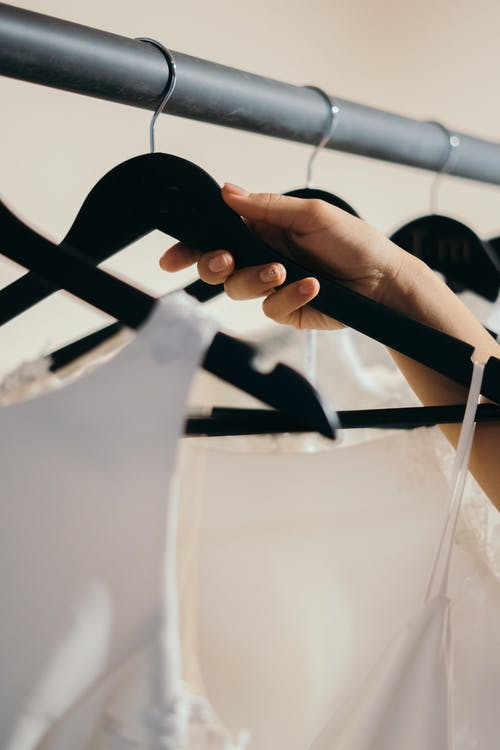 Close-Up Photo of a Person Holding a Black Hanger