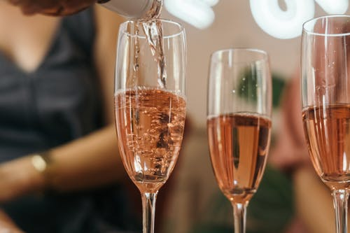 Close-Up Photo of Rosé Wine in Champagne Glasses