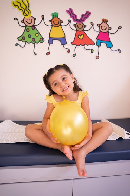 A Cute Girl Holding a Yellow Balloon