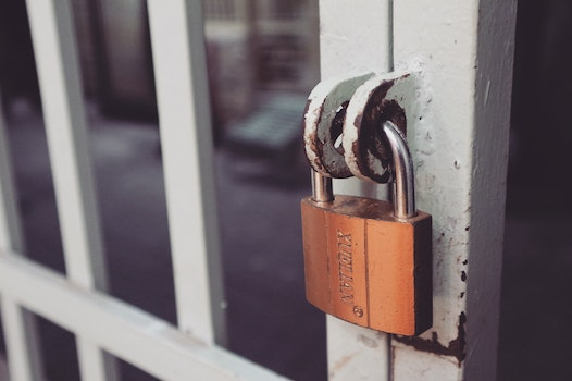 Closeup Photography of White Gate With Brass-colored Padlock