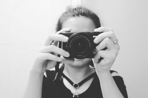 Grayscale Photo of Woman Holding Dslr Camera