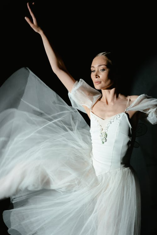 Woman in White Dress Raising Her Hands